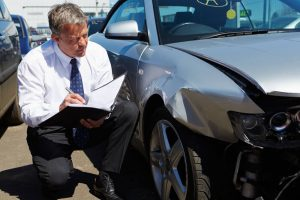 Photo of a man estimating the cost of a car repair